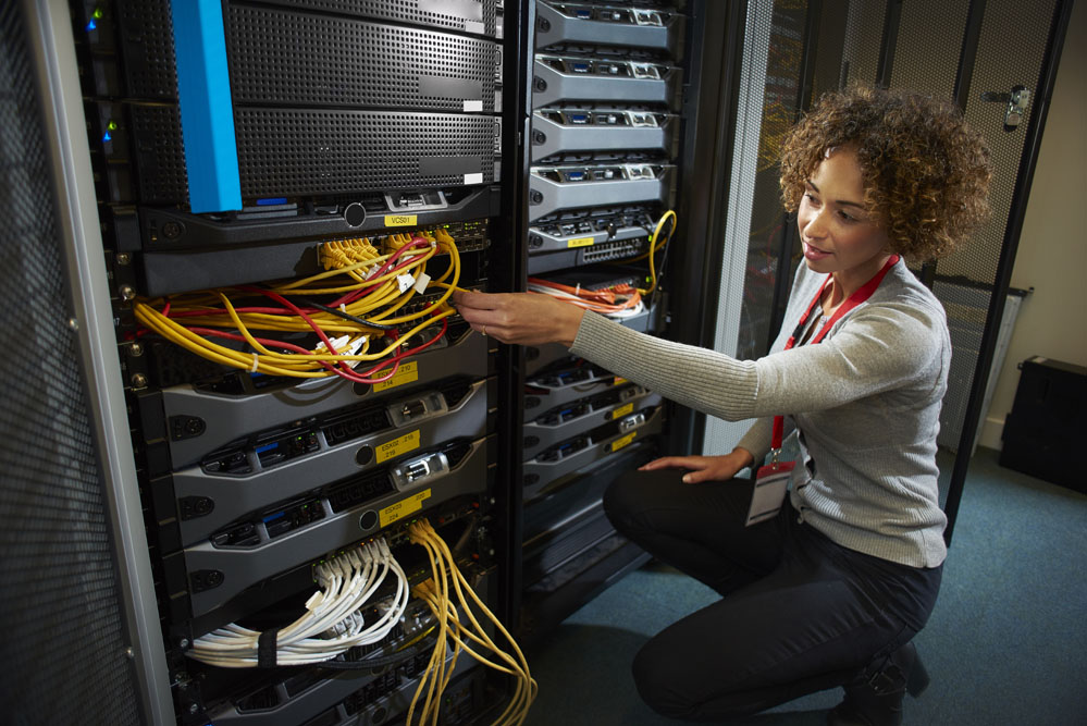 a female IT technician is editing the programme on the network server in a server room. ** all identifying script and racking has been modified **